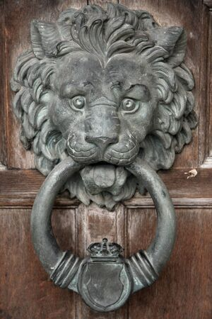 Lion's head door knocker, made of cast iron but tarnished by the years. A traditional design, also widely known as the Downing Street door knocker. Foto de archivo