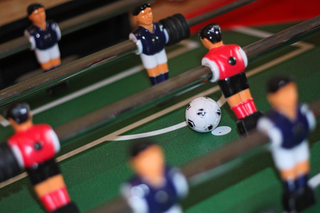 Close up of table football players in penalty area action. The ball is on the spot and there's a chance to score a goal.