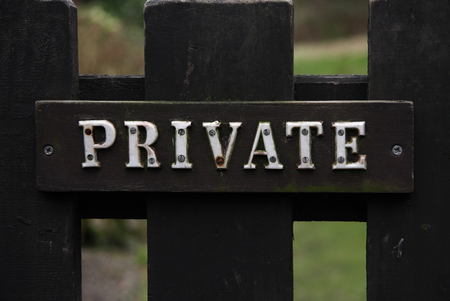 A private notice composed of individual letters screwed into a wooden plaque and fixed to a gate. Britain, UK