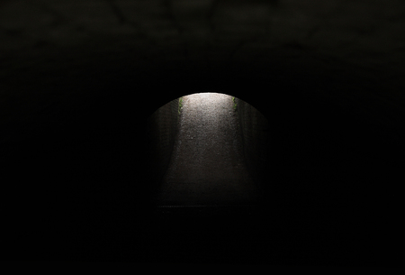 Daylight is visible beyond the arched exit of a dark tunnel, begging we emerge from the dark passageway. Worcestershire, UK