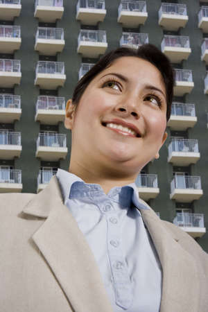 condos: beautiful young woman standing in front of a hotel or apartments.