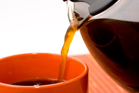 Pouring freshly brewed coffee from a pot to a coffee cup photo