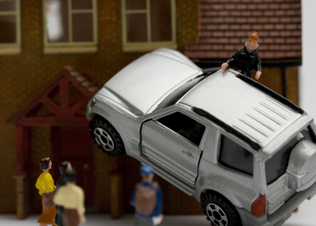 Miniature car crash into house with onlookers