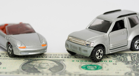 Miniature cars with one dollar bill under them Stock Photo - 1406389