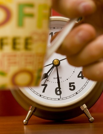Hand holding a cup of coffee with alarm clock in the background. photo