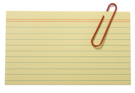 note card: Yellow lined paper fastened with a clip Stock Photo