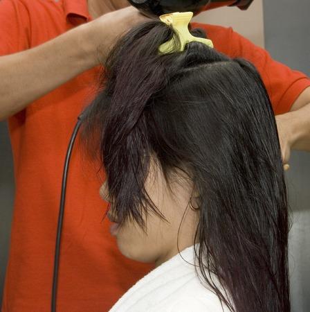 A woman getting her hair done by a hair dresser in a hair salon photo