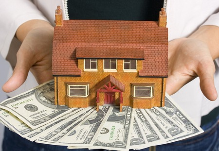 A person holding a miniature house and some dollar bills  photo