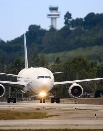 Airplane taxiing with control tower in the background photo