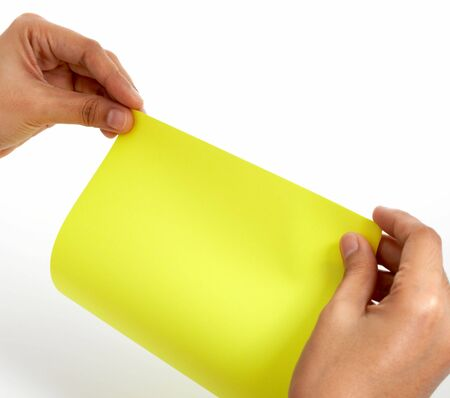 folding a piece of paper over a white background