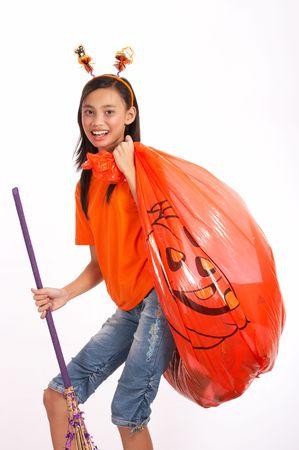 A young girl carrying a big pumpkin halloween bag Stock Photo - 2545156