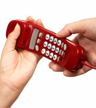 A hand passing a red phone while another hand reaches for it Stock Photo - 2539702
