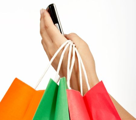 mobile shopping: a hand holding a cellphone and some shopping bags