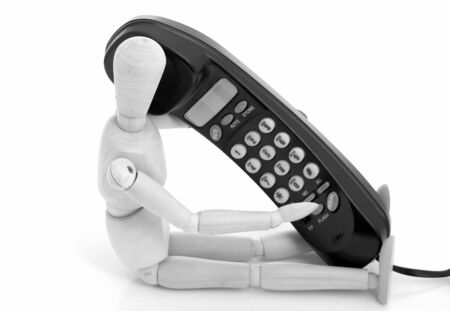 wooden figure: wooden figure holding a black telephone over a white background Stock Photo
