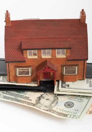 Miniature house over a leather wallet with dollars Stock Photo - 2567769
