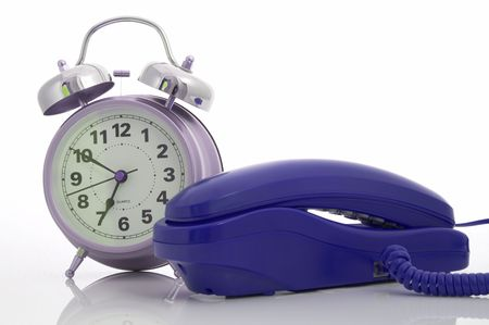 Photo of a telephone and an alarm clock over a white background Stock Photo