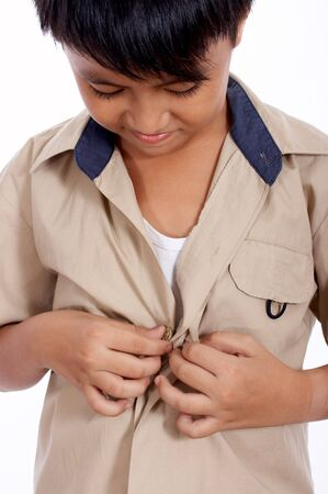 young boy looking down fixing his clothes photo