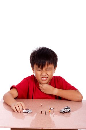 child under meditation of sore throat playing toy car Stock Photo