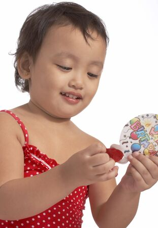 little girl in red dress holding party popper Stock Photo - 3121424