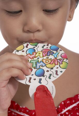 party popper: young toddler girl blowing a party popper