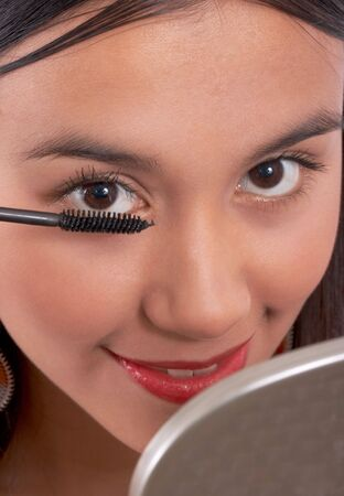 close-up shot of a girl applying black mascara photo