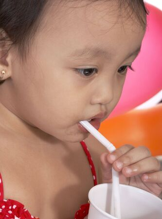 sipping: child sipping juice on a white plastic cup Stock Photo