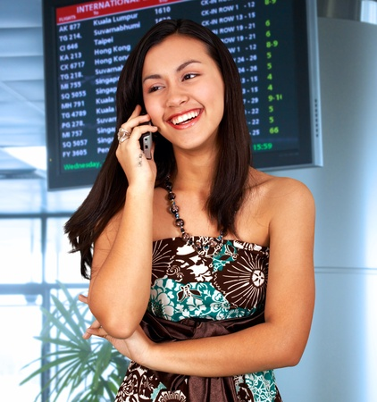 calling on phone: Young woman in an airport talking on the phone