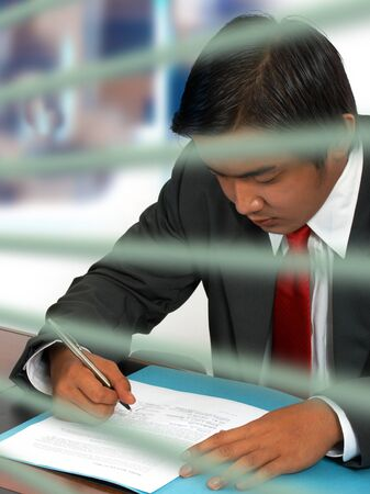Businessman reading and signing a document photo