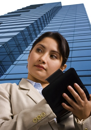 A business woman writing in a personal organizer and standing in front of a tall skyscraper Stock Photo - 9631642