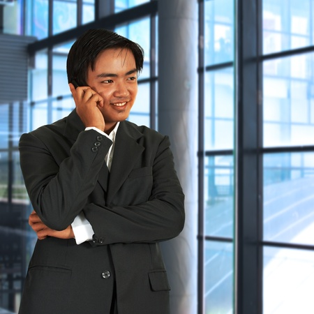 bussines: Zakenman chatten op de telefoon voor Windows In zijn kantoor Stockfoto