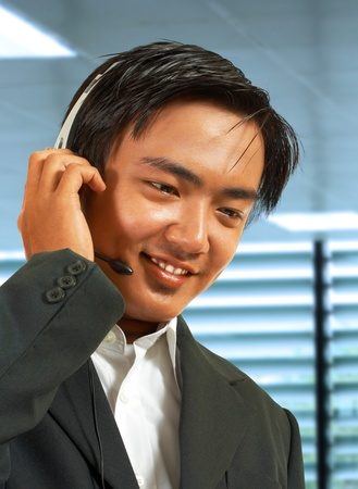 Male Sales Representative In His Office Talking On A Headset To A Customer photo
