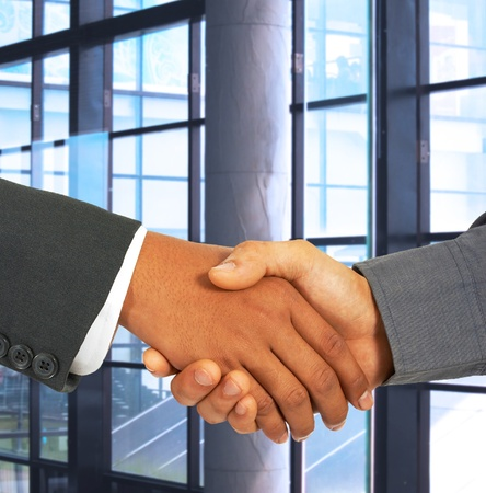 2 Businessmen In An Office Shaking Hands To Seal An Agreement photo