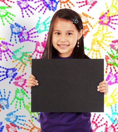 Young Cheerful Girl With A Blank Board And Wall With Colored Hands In The Background photo