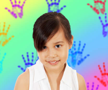 A Shy Young Girl In Her Play Room With Multicolored Hand Prints On The Wall photo