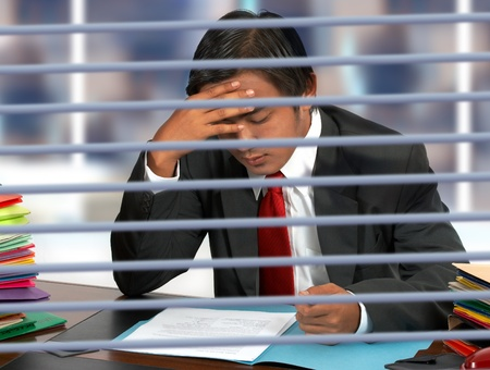 Businessman in his office reading documents photo