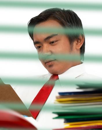 bussines: Man zit op zijn kantoor bureau en het lezen van een document in een map