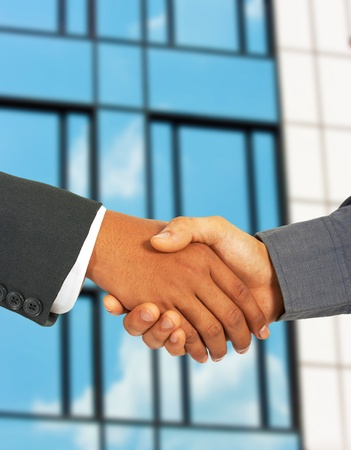 Businessmen Greet Each Other By Shaking Hands - Outside With An Office Building Background photo