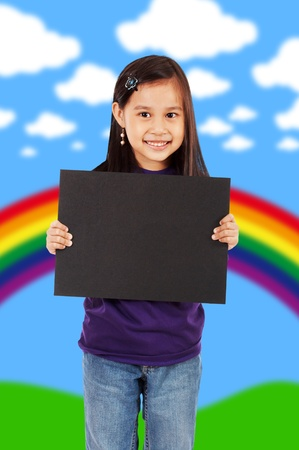 A Smiling Girl Holding A Blank Black Board With An Abstract Rainbow And Clouds Background  photo