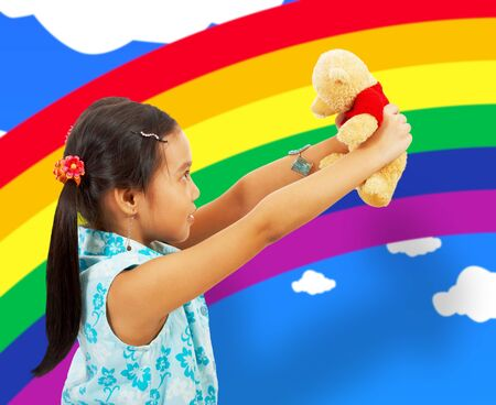 Young Girl Playing With Her Teddybear In Her Playroom With Rainbow Wallpaper photo