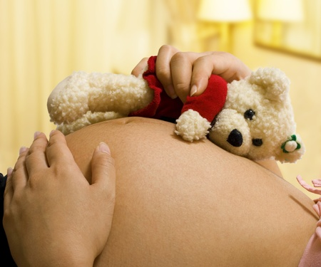 Expectant mother in her bedroom holding a teddy bear photo