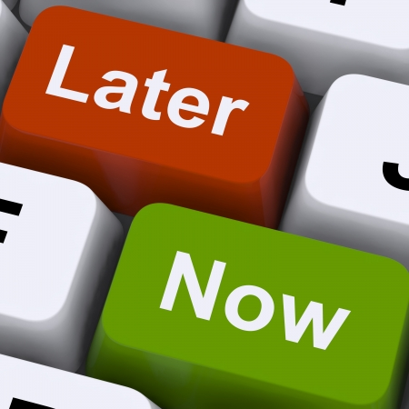 procrastination: Now Or Later Keys Showing Delay Deadlines And Urgency Stock Photo