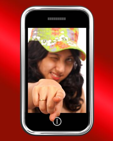 Young Asian Girl Pointing Out Of Mobile Phone photo