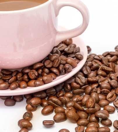 hot coffees: Coffee beans next to a cup of new freshly brewed