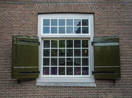 sash: An old georgian sash style window on a brick house in Amsterdam with wooden shutters Stock Photo