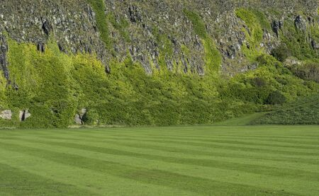 kept: Landscape shot of a well kept lawn infront of a steep cliff face which is overgown with heather Stock Photo