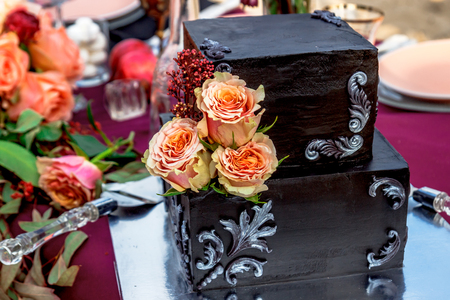 Black wedding cake with natural roses
