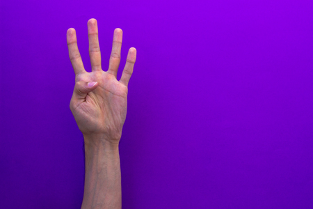 Four counting hands isolated on purple background
