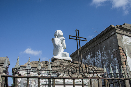 The statue of a prayerful young girl sits atop an above-ground burial vault in St  Louis Cemetery Number One in New Orleans, Louisiana photo