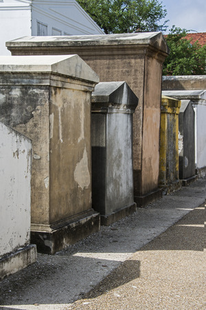 Weathered above ground burial vaults in the St  Louis Cemetery Number 1 in New Orleans, Louisiana cast shadows on the path that runs in front of them photo