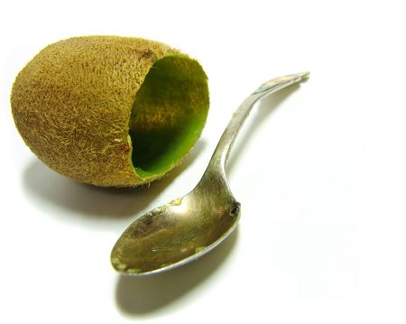 Closeup of a hollow  kiwi fruit with a teaspoon on white background Stock Photo - 338166